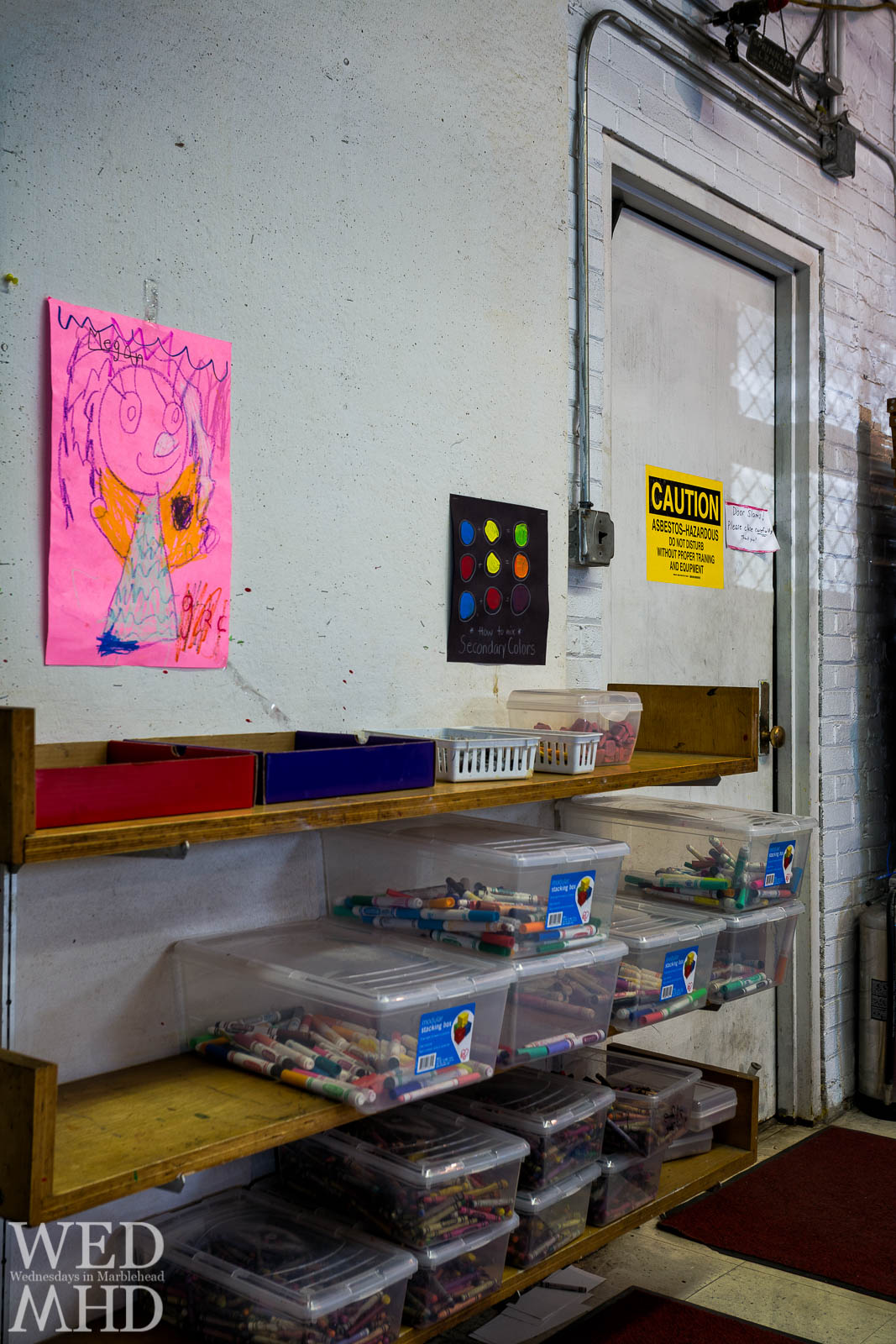 A sign cautions about asbestos exposure near art supplies and a child's drawing at the Gerry School