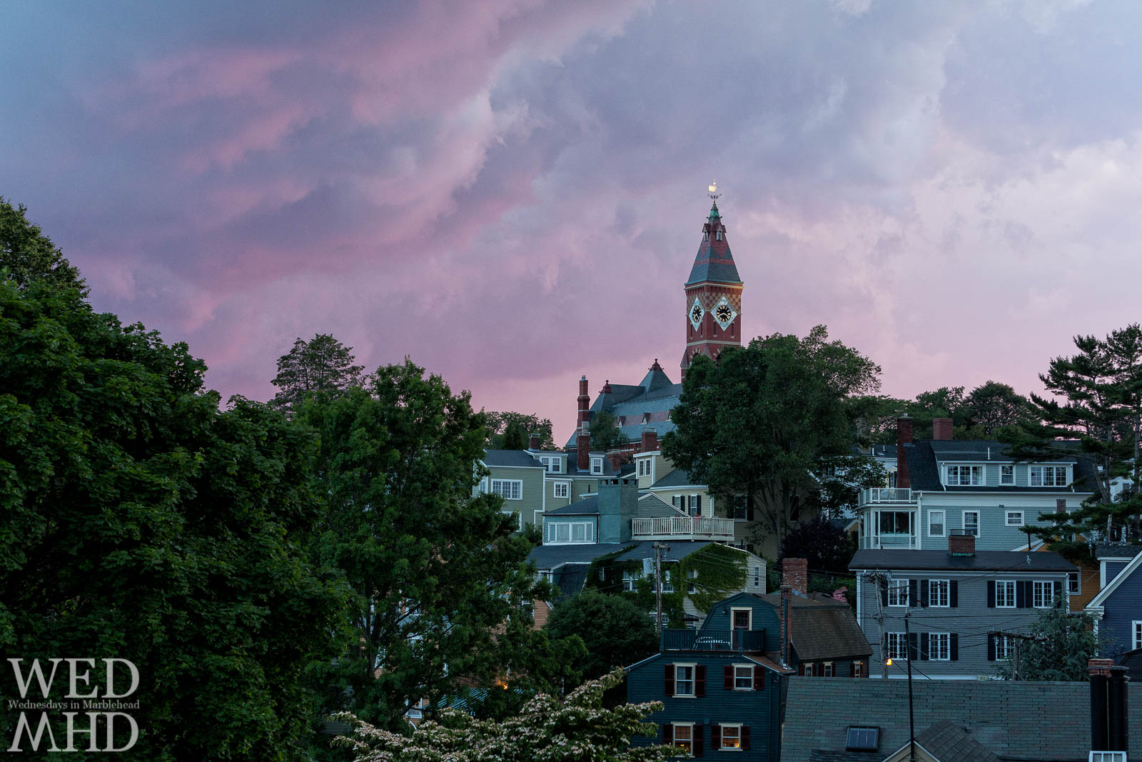 A dramatic purple sunset forms over Marblehead on July 1st as the setting sun illuminates Abbot's golden weathervane