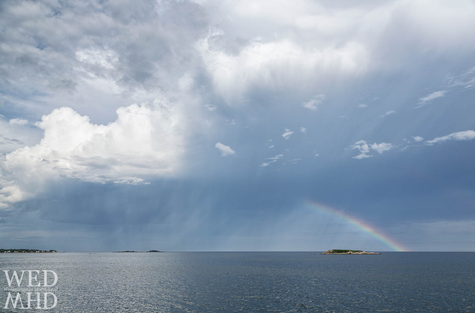 A rainbow intersects with rain clouds over Ram Island on a mid-Summer evening