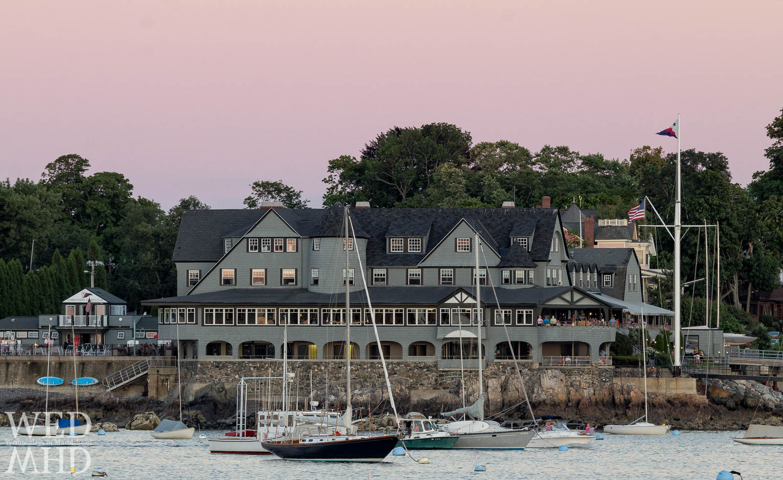 Evening light colors the sky pink over the Corinthian Yacht Club with boats moored in the harbor