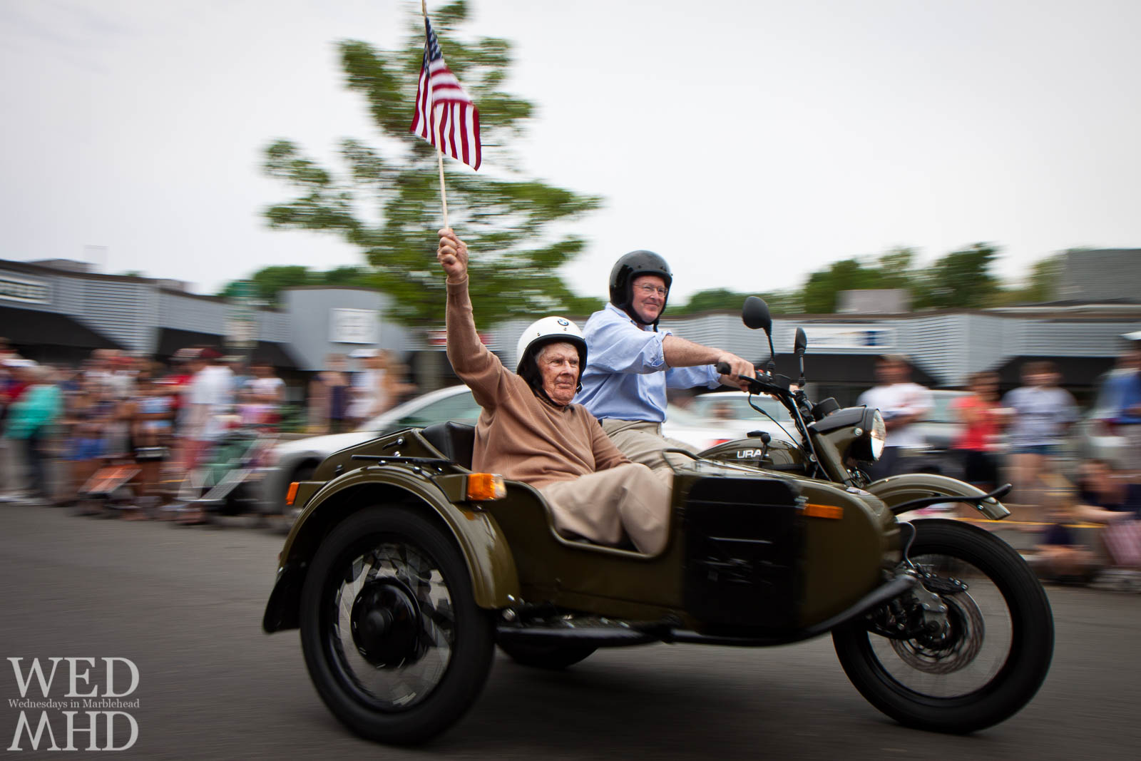 A proud veteran rides in the sidecar of an antique military motorcycle during the Marblehead Memorial Day parade while raising the flag high in the air