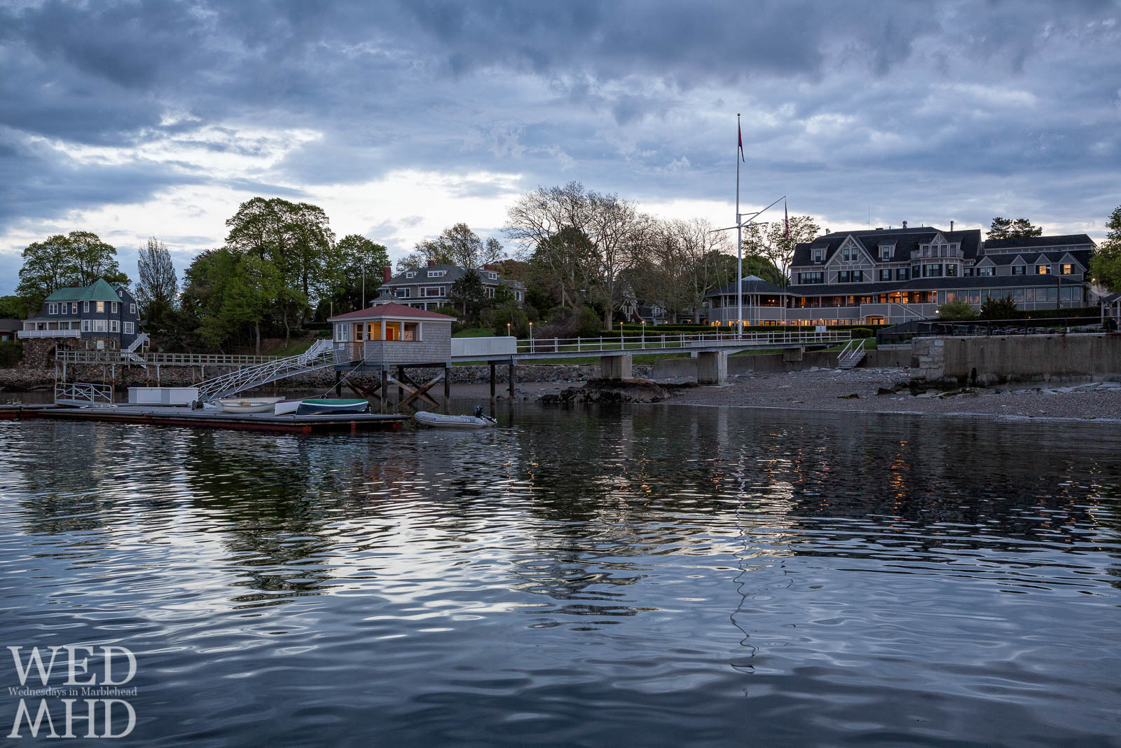 The lights of the Eastern Yacht Club are reflected in the still waters of Marblehead Harbor at sunset
