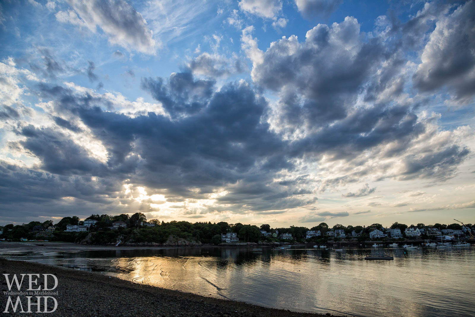 The setting sun forms rays of light through clouds and paints the golden water of Riverhead Beach
