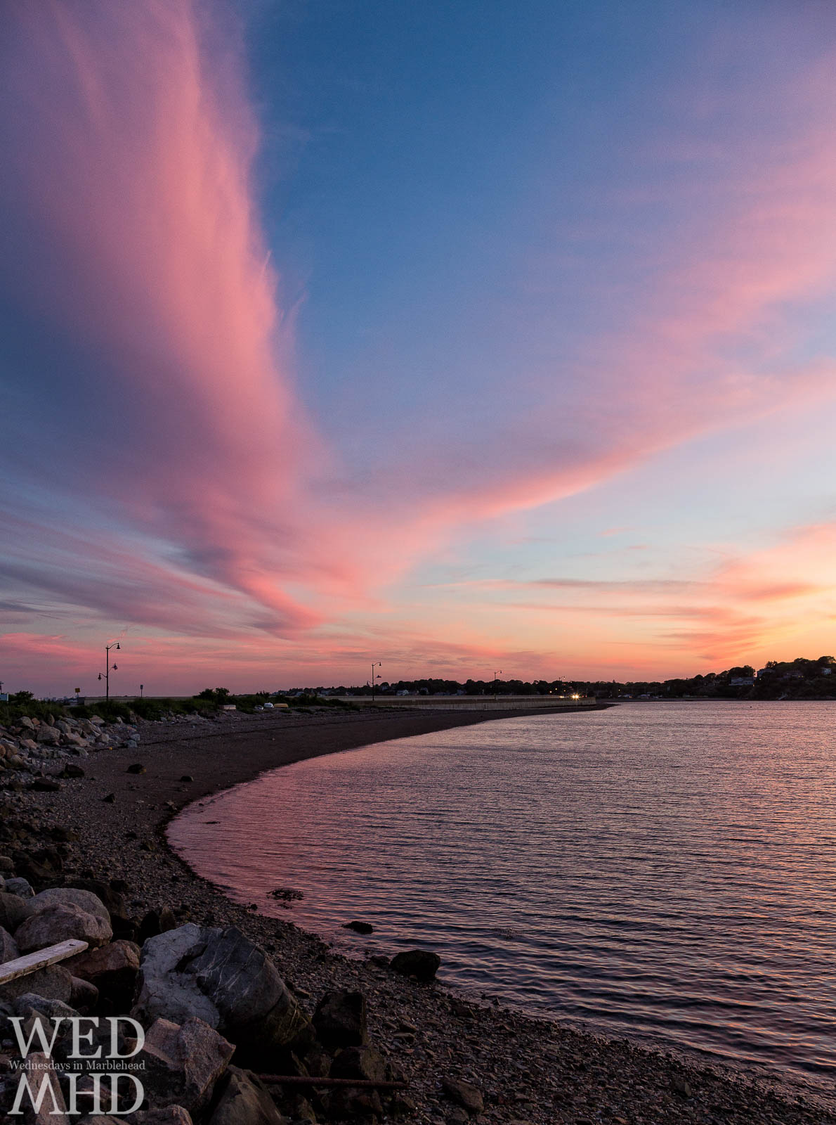 A large clouds reflects sunset light to form a pink sky over Riverhead Beach