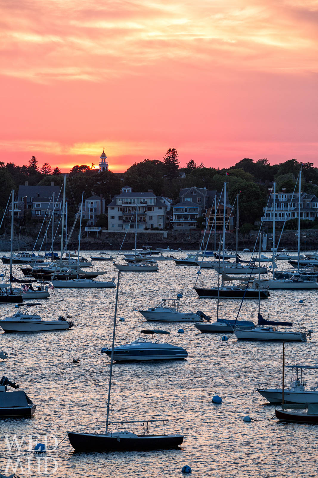 A red sky at night serves as backdrop to Old North Church and homes along Marblehead Harbor