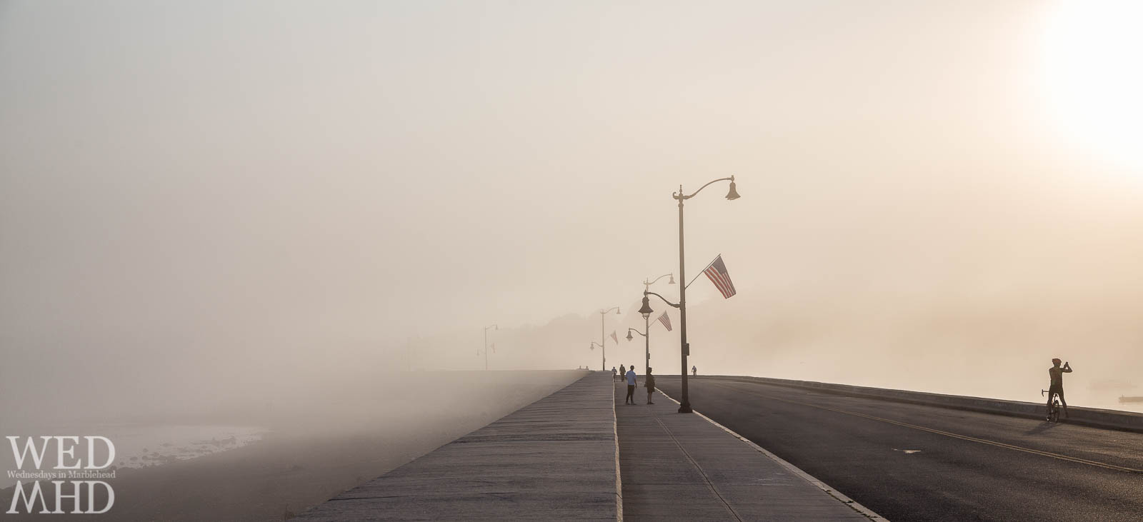 A bicyclist stops along the causeway to capture the fog rolling into Marblehead Harbor