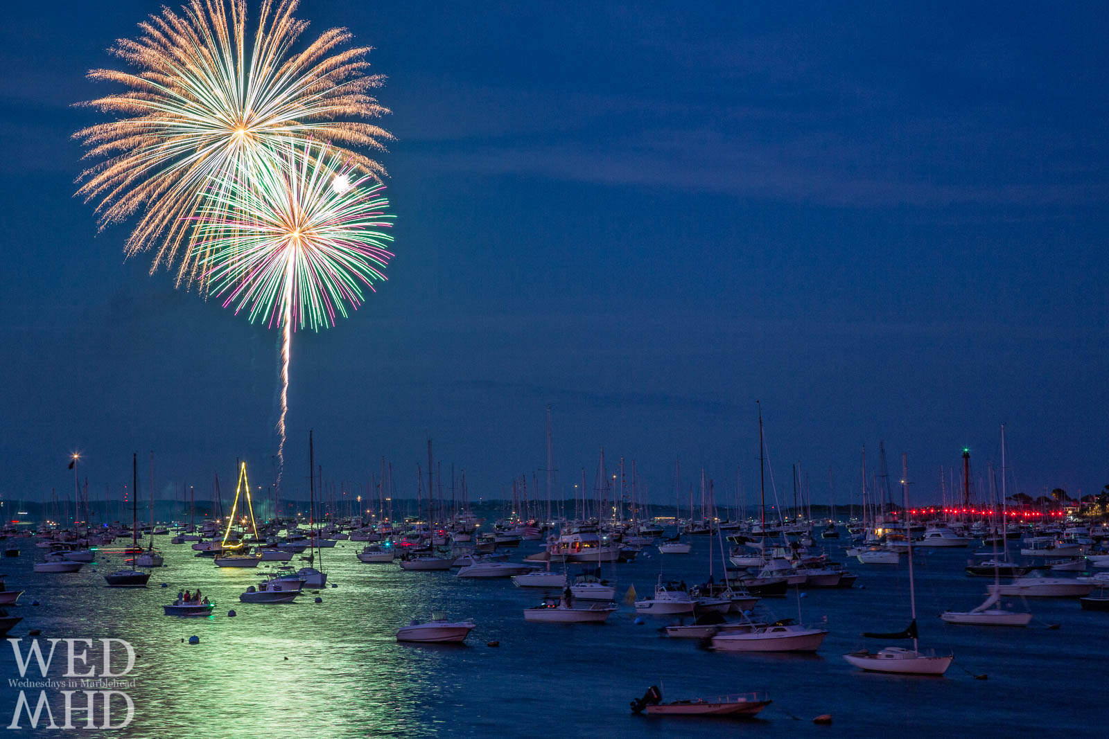 Two fireworks explode over Marblehead harbor with boats gathered underneath to watch the annual show