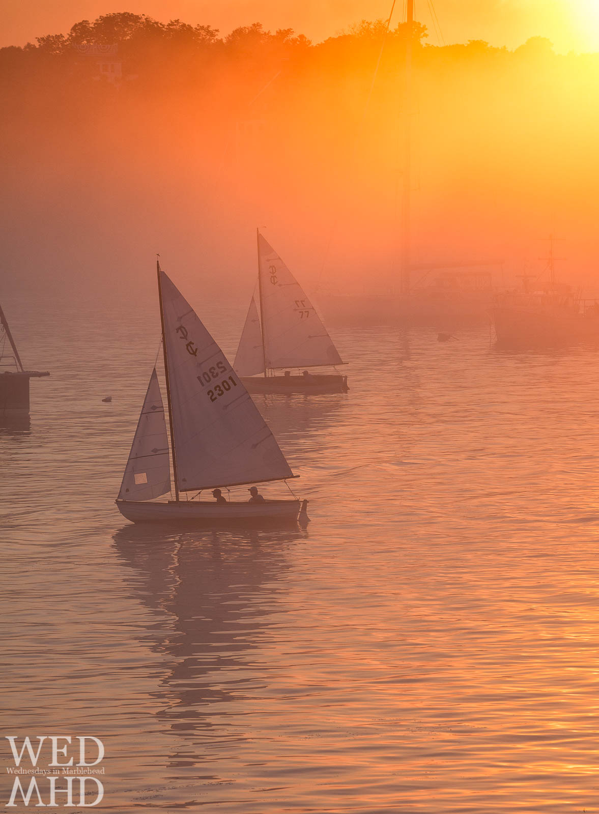 A late fog creates incredible backlight for two boats sailing under the sunset into Marblehead harbor
