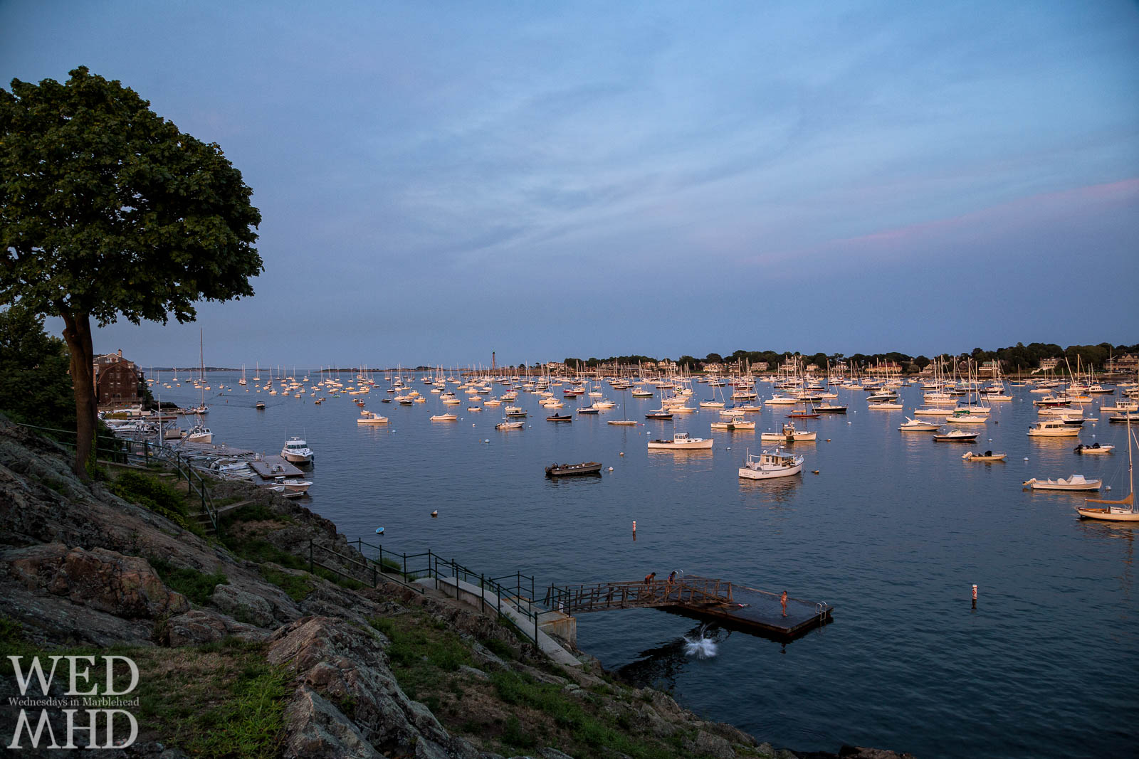 Kids caught diving at dusk from the Crocker Park float on a warm Summer night in Marblehead