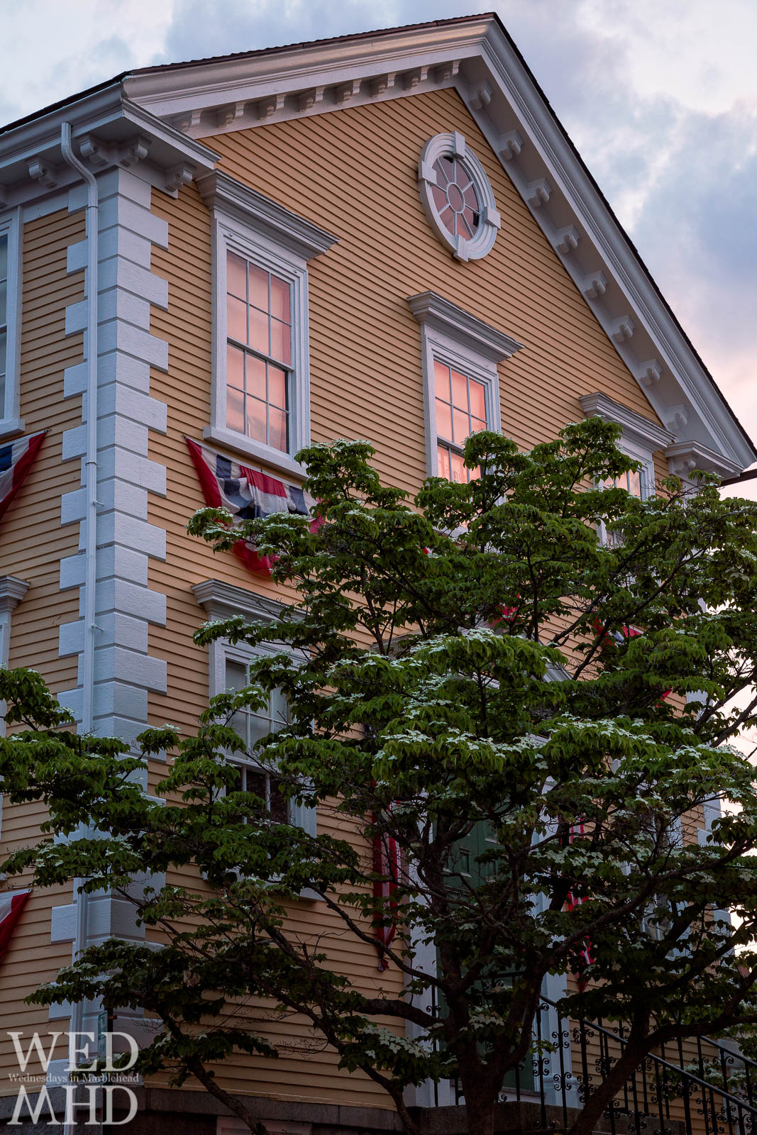 Old Town House is bathed in a pink glow reflecting in its windows just after the sun sets