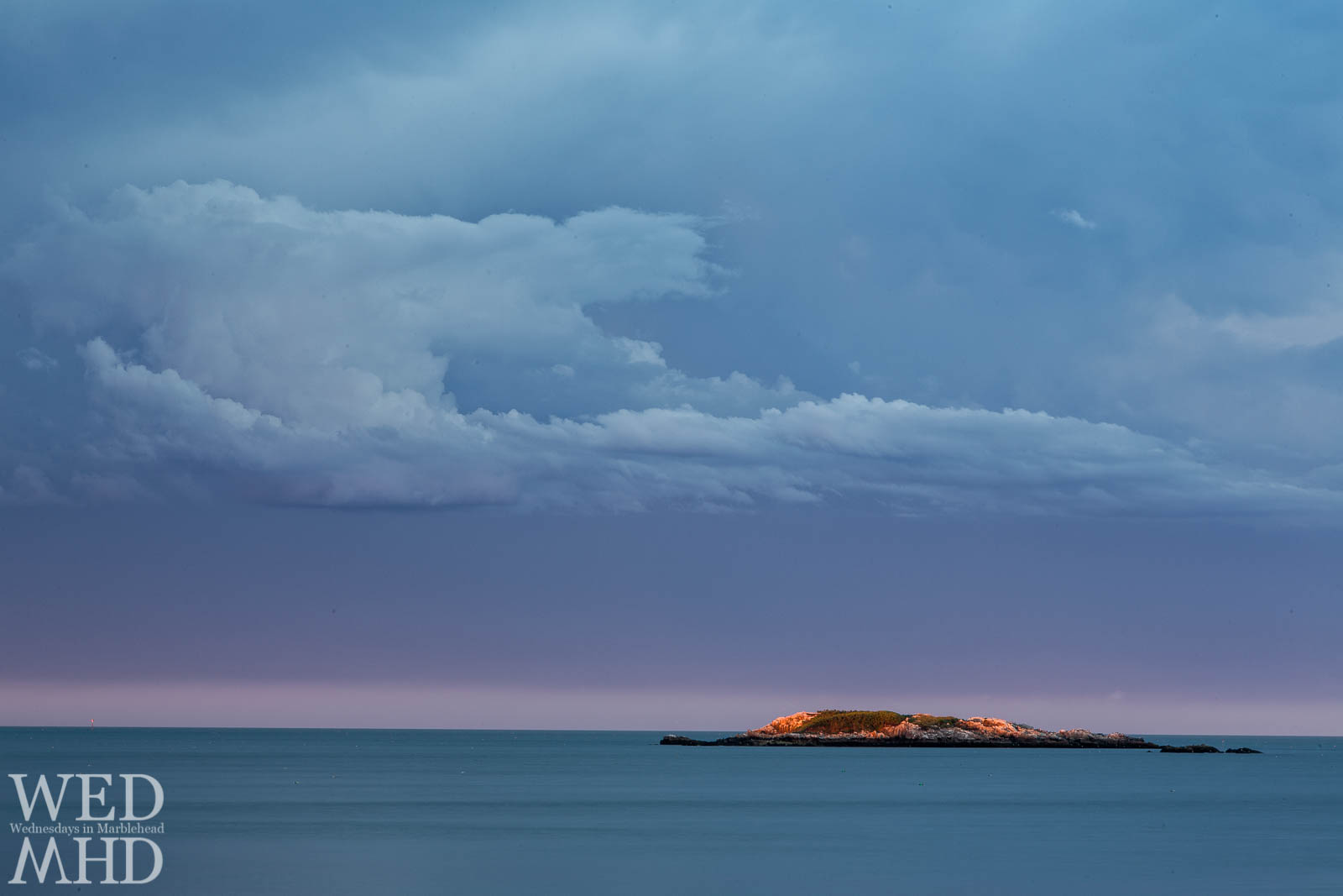 A long exposure smooths the ocean while capture clouds as the last light of sunset bathes Ram's Island