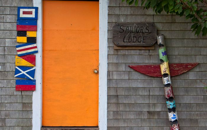 The bright orange door, flags and winged column mark the Sailors Lodge on Childrens Island