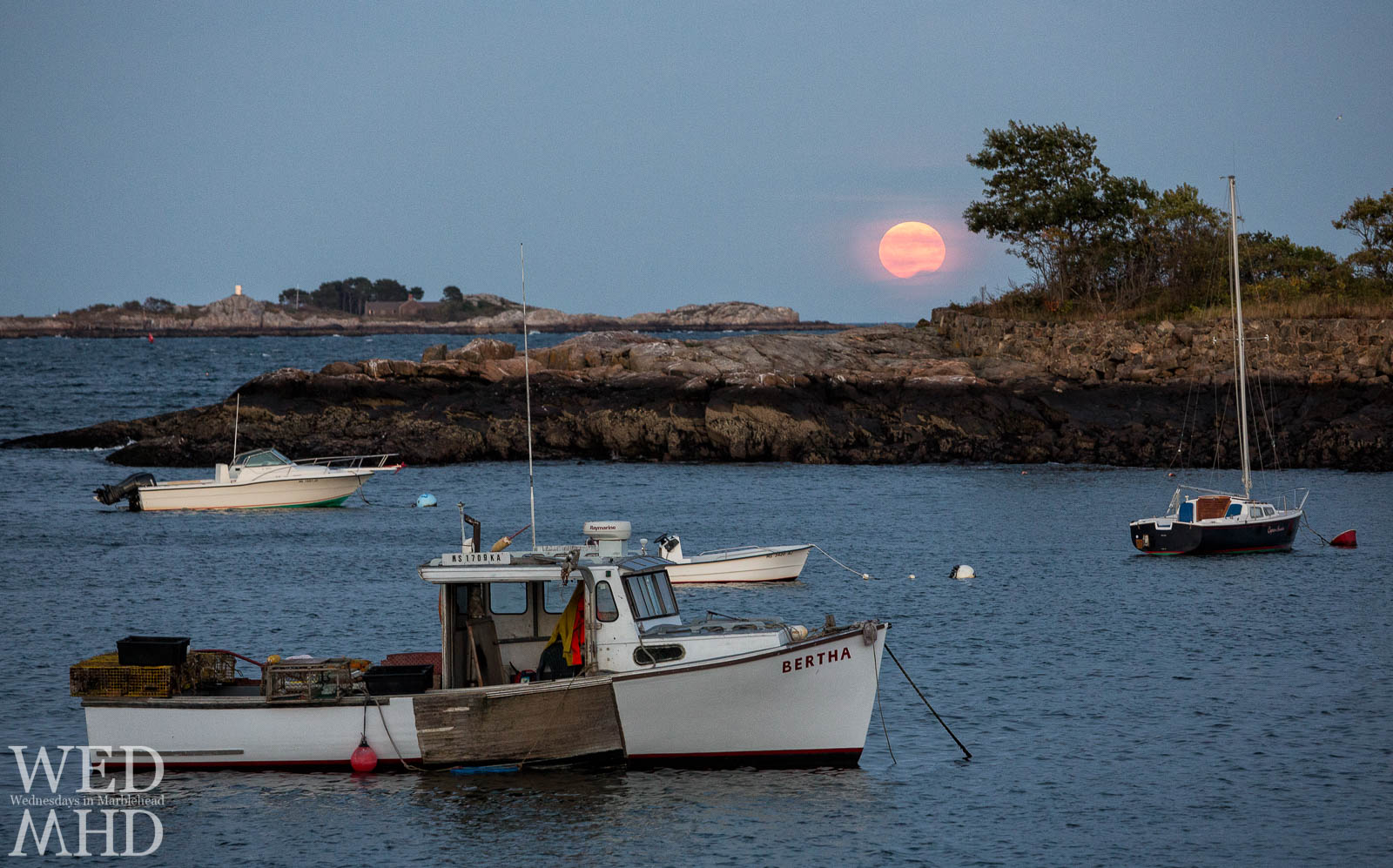 The working boat Bertha is moored in Little Harbor as the Harvest Moon rises over Marblehead