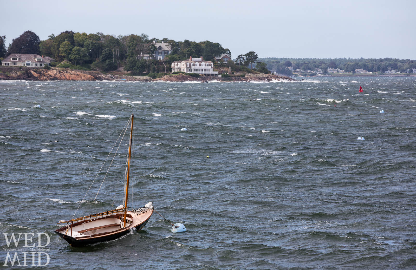 A lone boat caught fighting the current created by an offshore storm while moored at the mouth of Marblehead Harbor