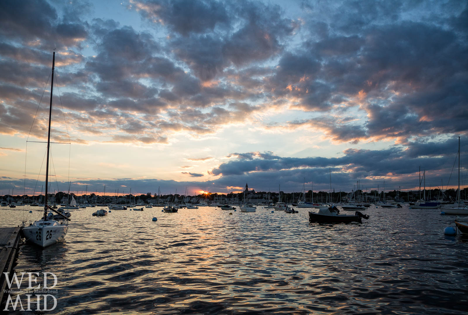 A view from water level captures the last rays of light over Marblehead Harbor with boats in their moorings and clouds reflecting the light of sunset