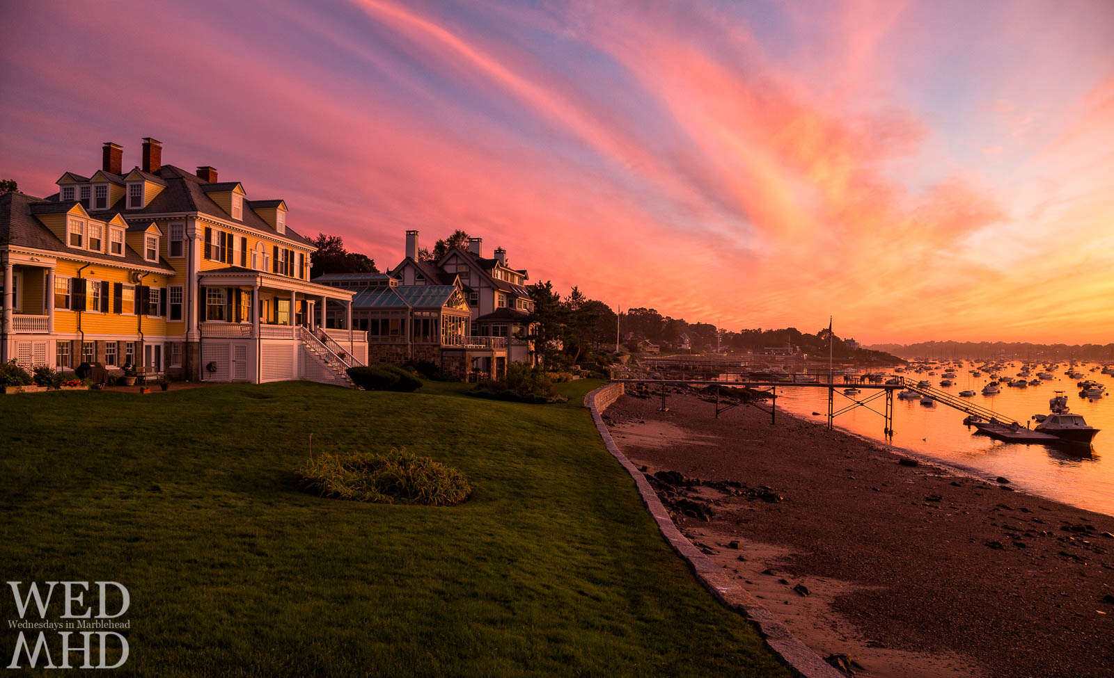 A beautiful sunset takes shape over Marblehead Harbor and reflects on these houses in a typical Summer night on the Neck
