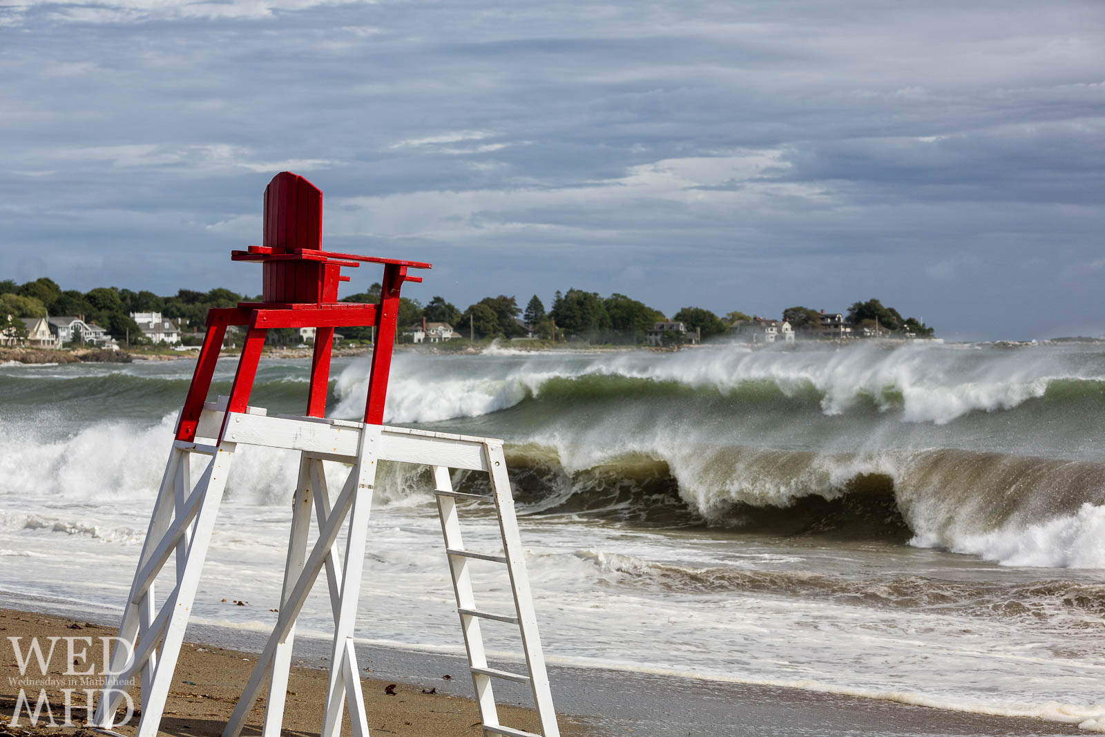 A lifeguard chair stands empty as huges waves come ashore meaning guards are off duty at Devereux Beach