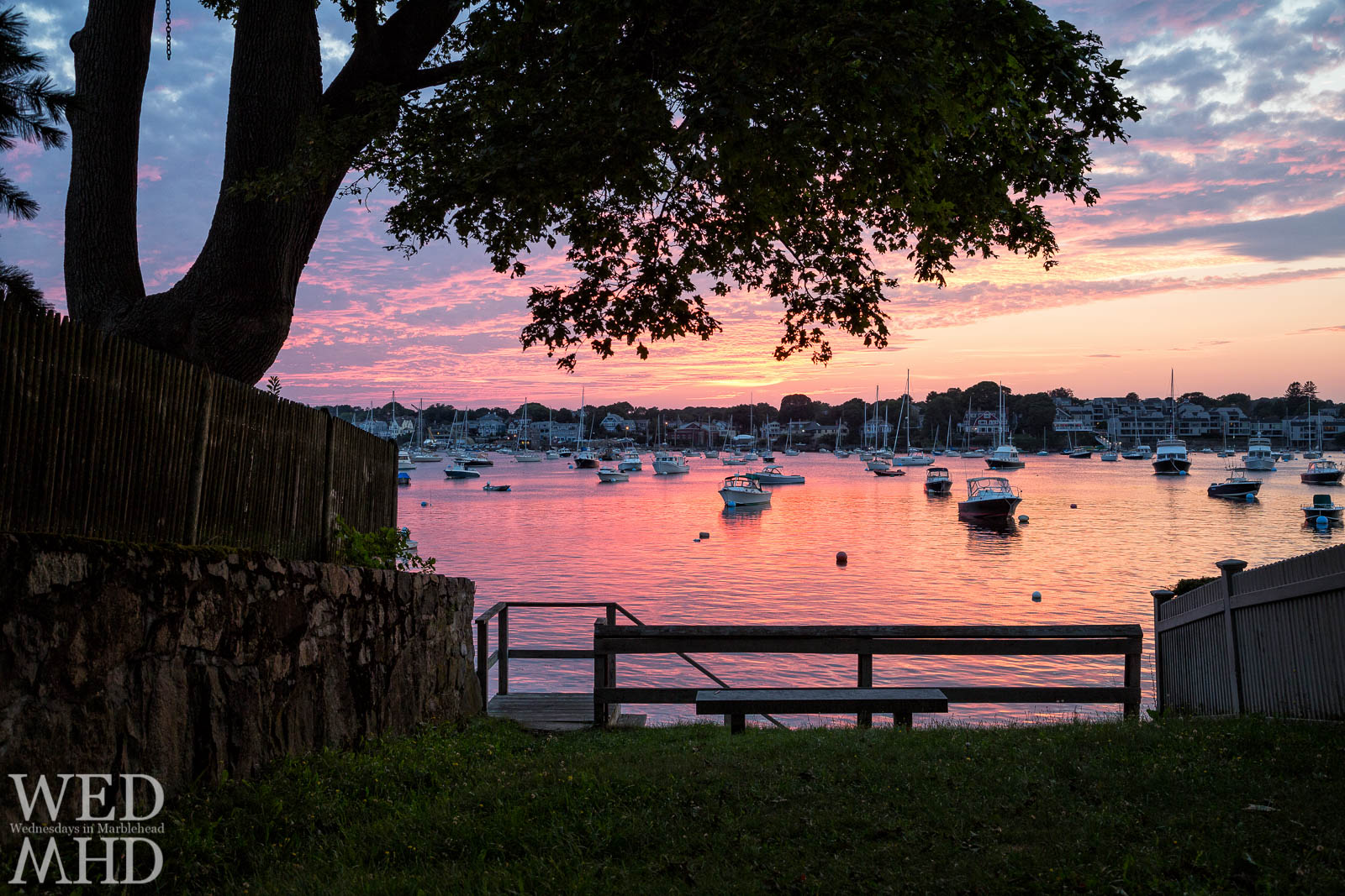 A Summer sunset at Parker Lane bathes the sky and water in color as seen from this public way on Marblehead Neck