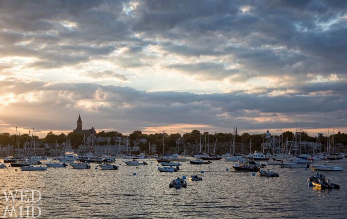 The soft glow of sunset bathes boats moored in Marblehead Harbor