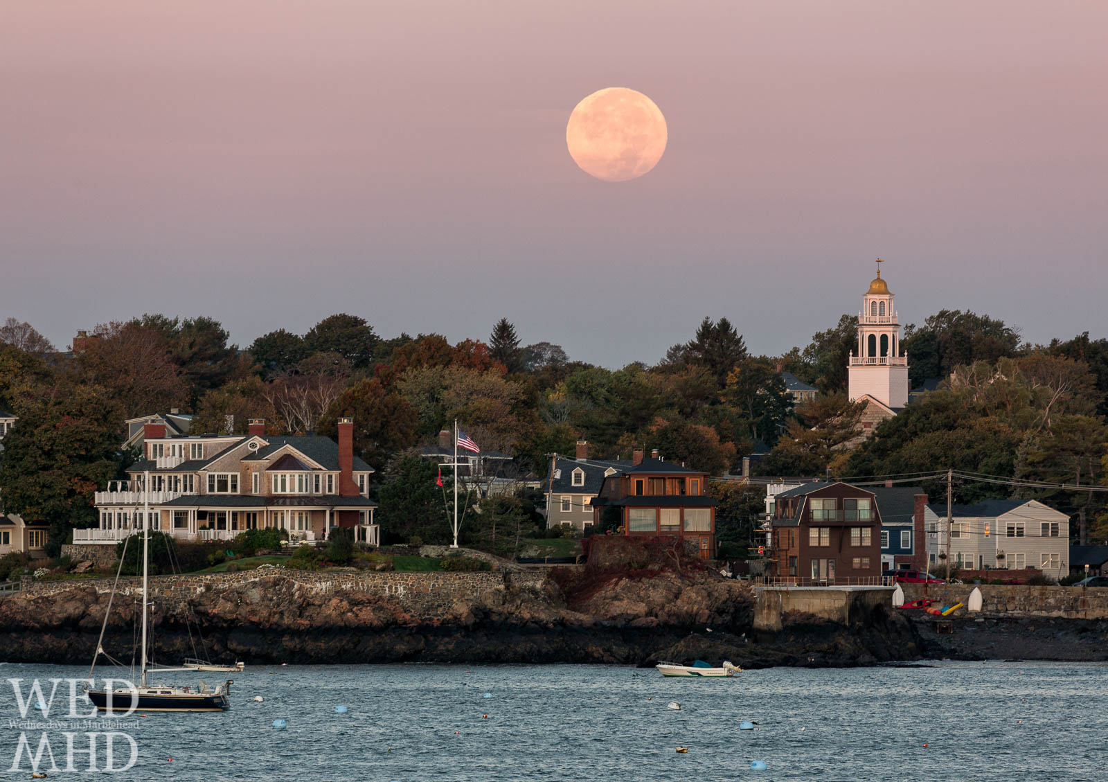 The full Hunter moon sets over Old North Church in Marblehead appearing larger than normal due to its proximity to Earth
