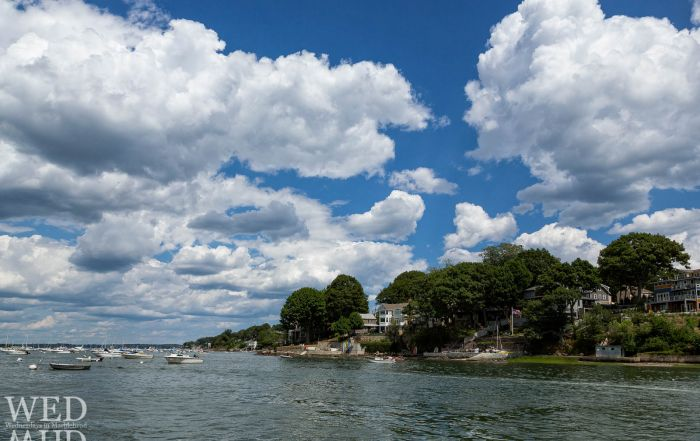 A view of life on the West shore of Marblehead with perfect cloud filled skies and boats moored in Salem harbor