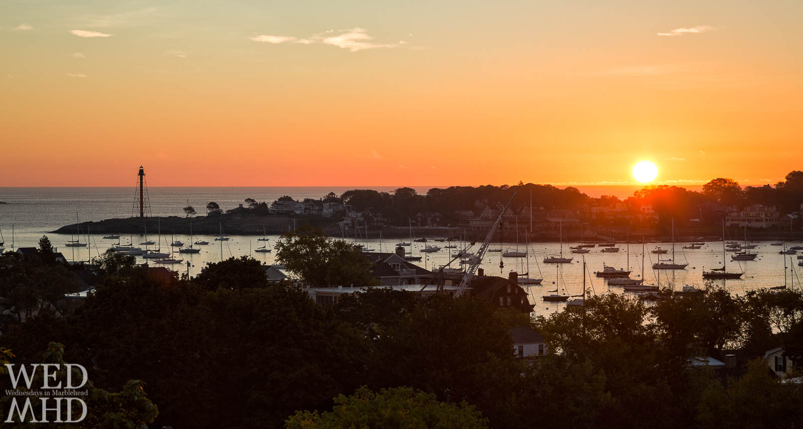 A brilliant sunrise over Marblehead Neck bathes Marblehead Harbor in an orange glow and is reflected by Marblehead Light