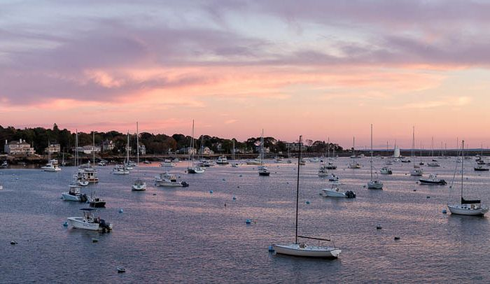 A beautiful sunset forms over inner Marblehead harbor on a mid-October evening with boats still moored and awaiting the last sails of the season