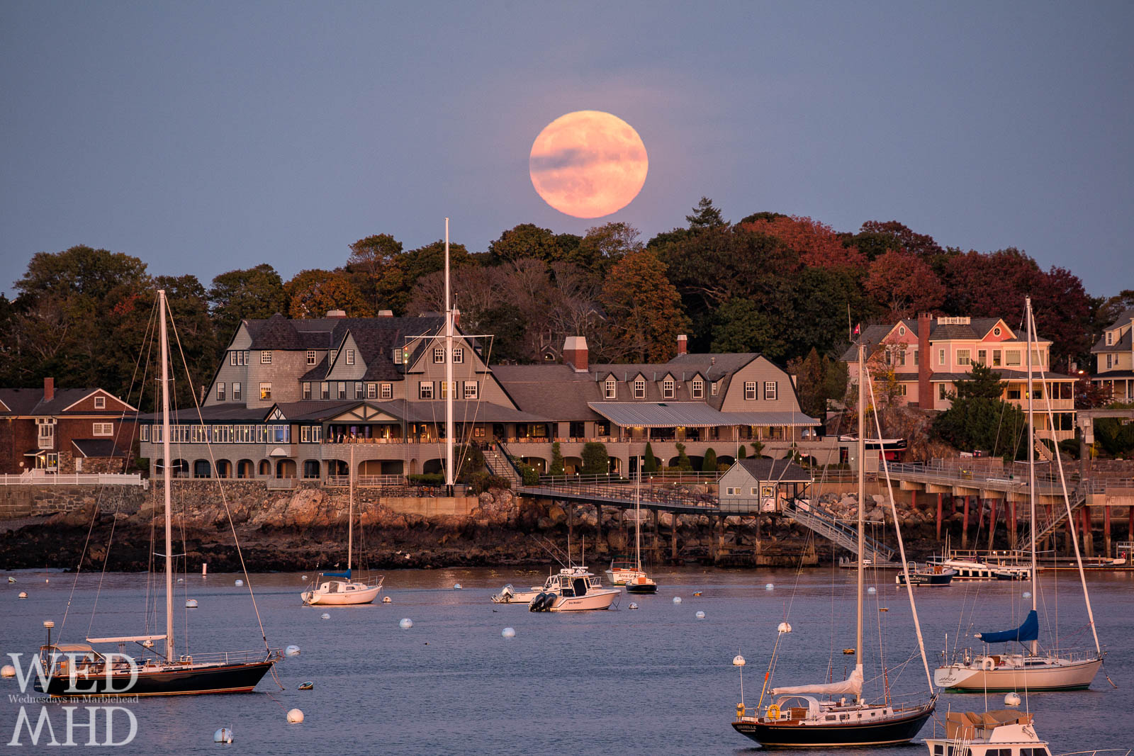The Hunter moon rises over the Corinthian Yacht Club with hints of foliage in the trees and boats still moored in the harbor