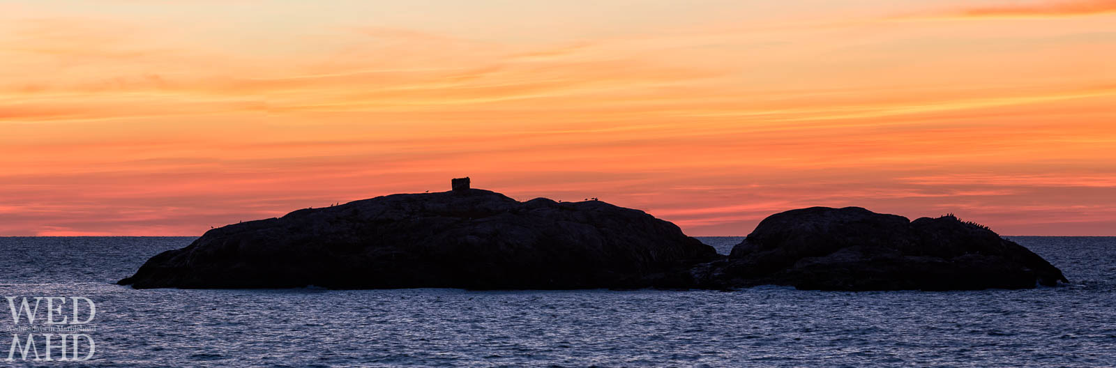 A panoramic view of Marblehead Rock captured under an orange sky at dawn on a mid-October morning