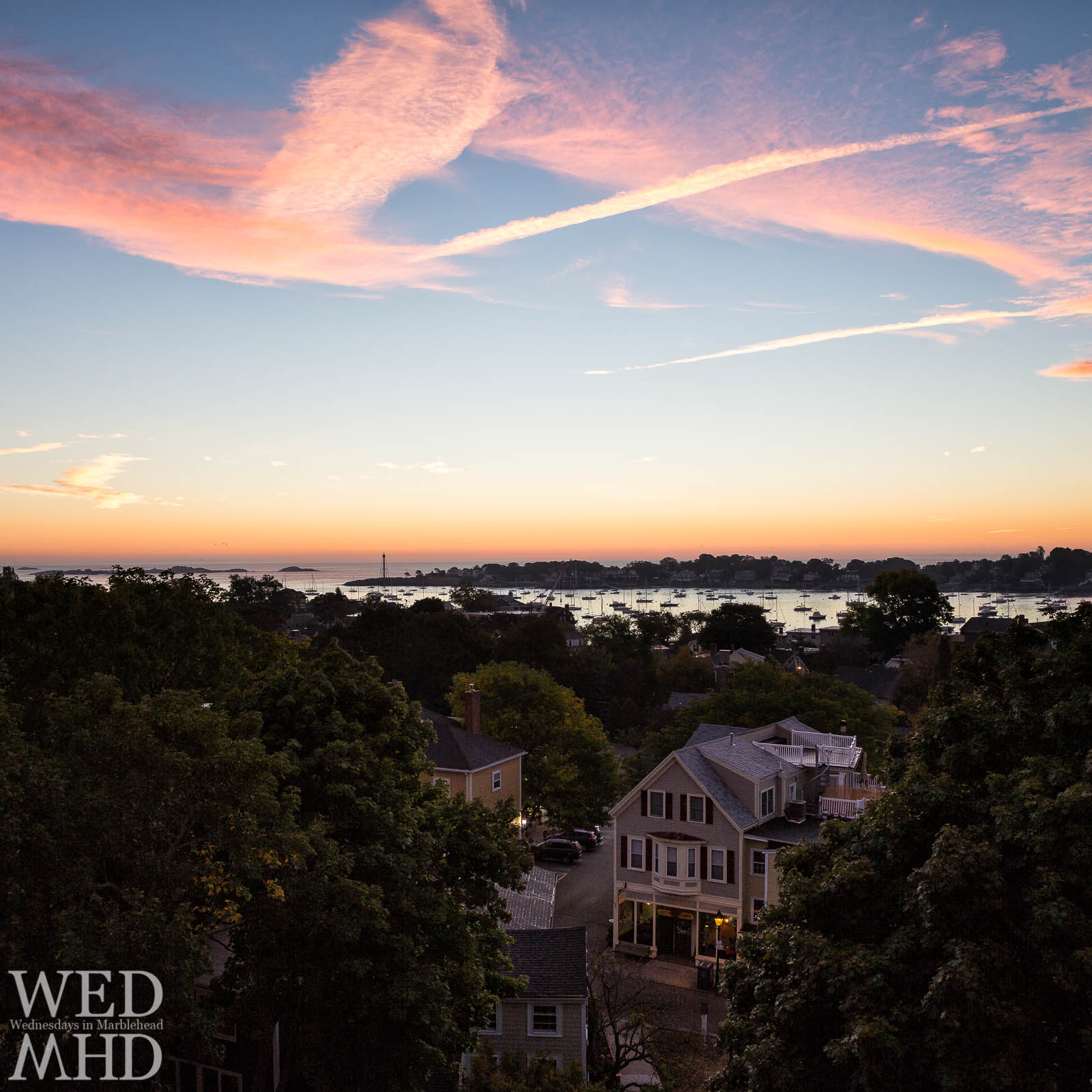 A rooftop view of the Muffin Shop at dawn with Marblehead harbor and its lighthouse in the distance
