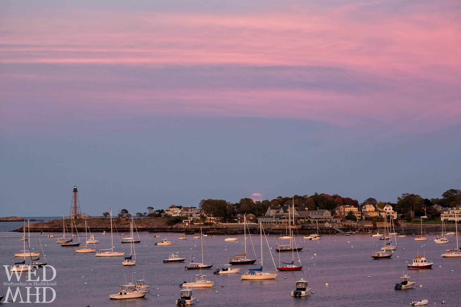 A pink sky forms as the first hint of moonrise peaks beyond the treeline on Marblehead Neck