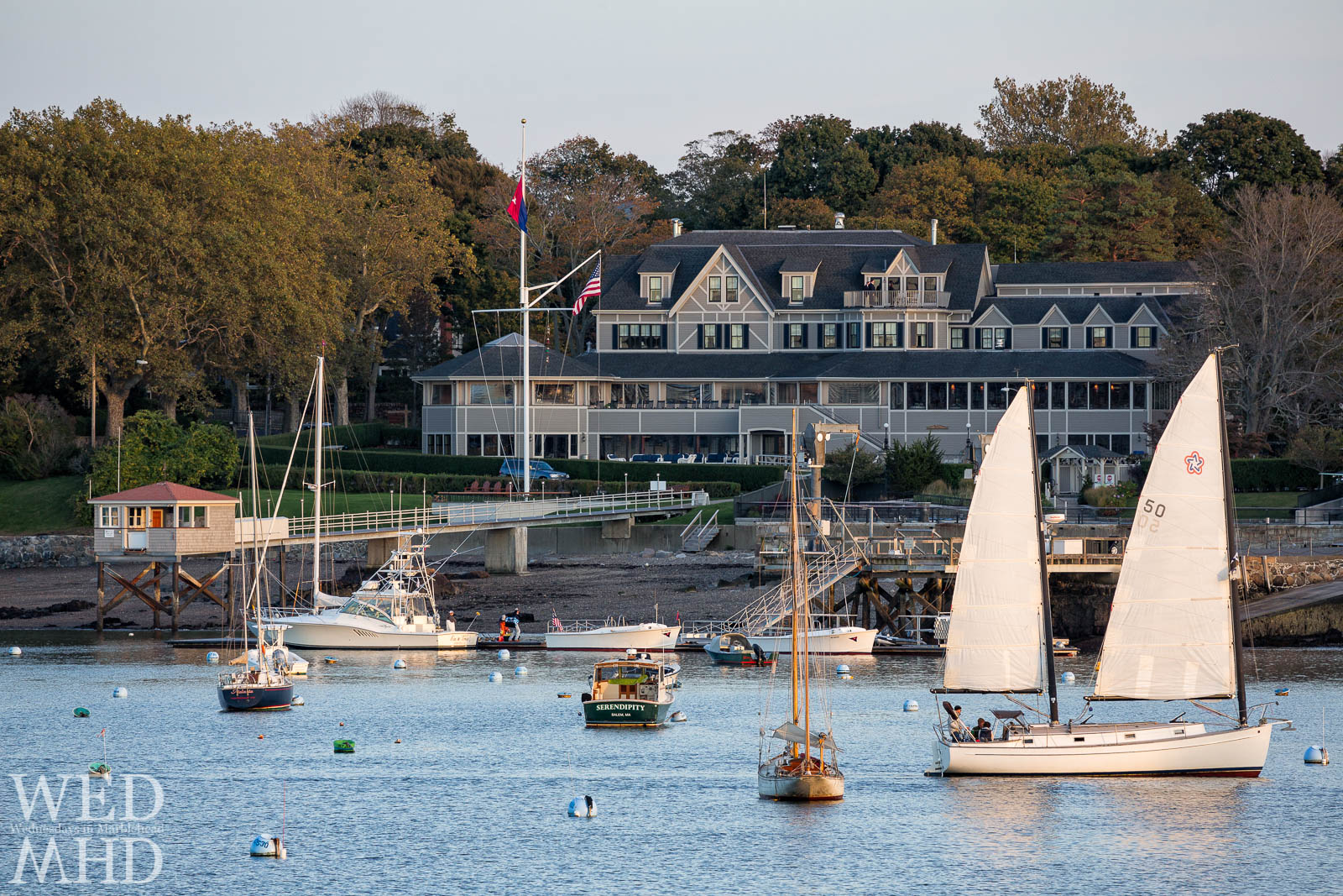 A boat's sails reflect the light of the evening sun while sailing past the Eastern Yacht Club toward its mooring