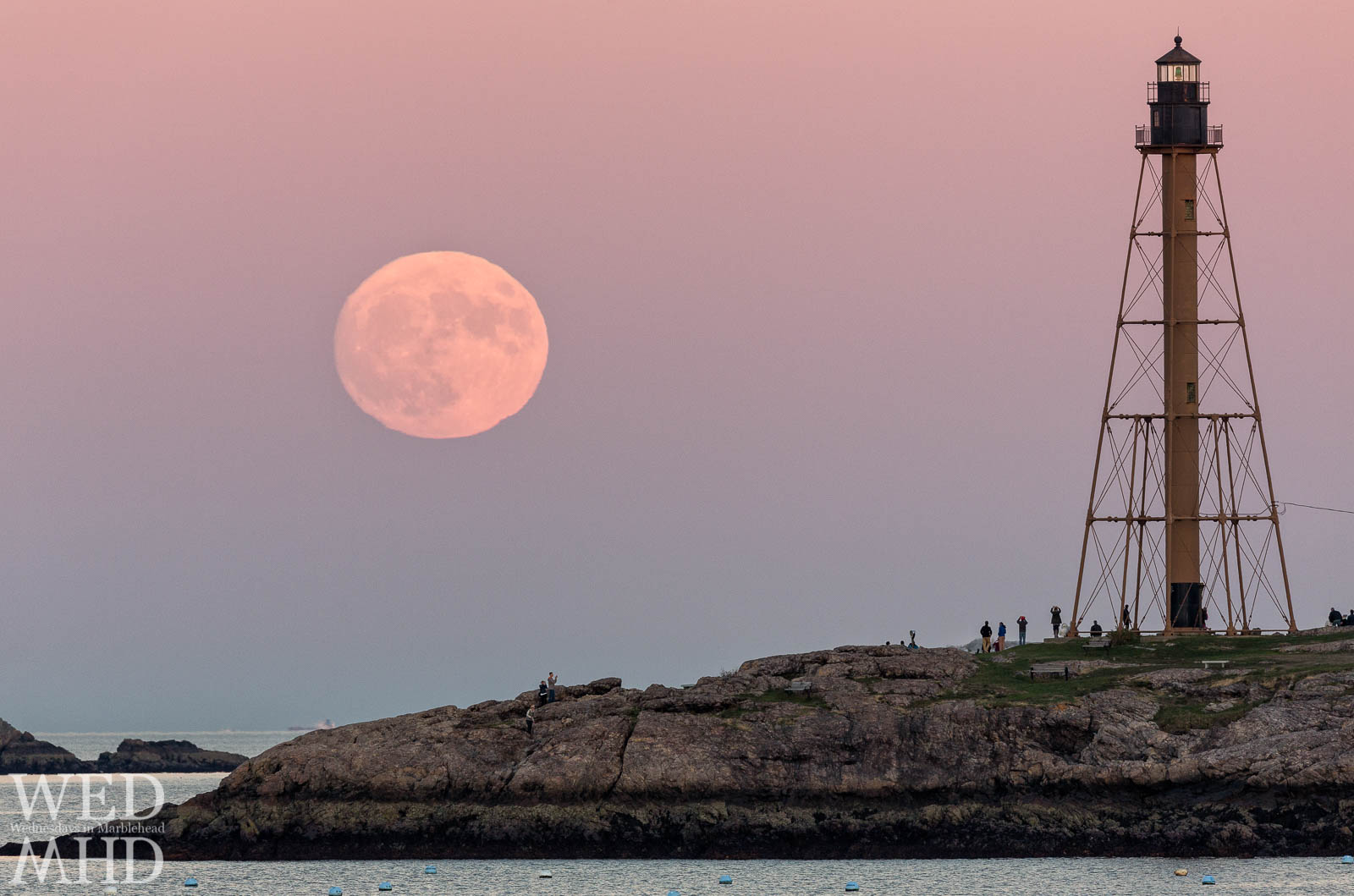The supermoon rises over Marblehead Light as the largest full moon in over 60 years. Crowds gather at Chandler Hovey Park to watch the display.