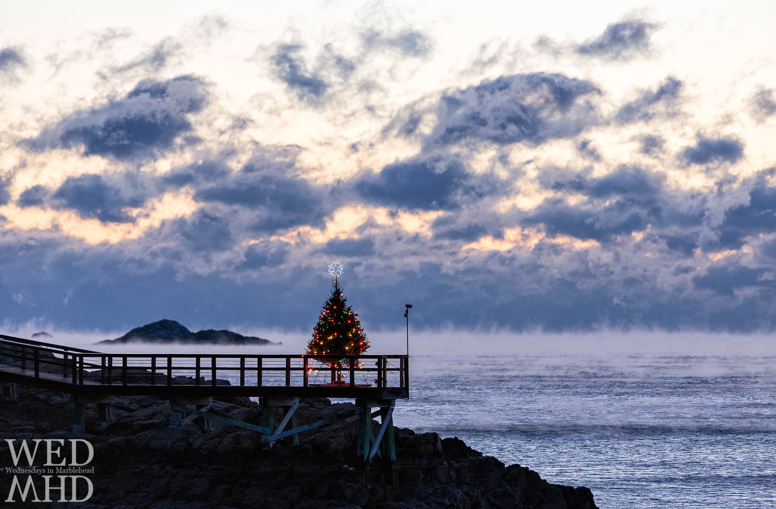 A Christmas tree at the end of a pier is surrounded by sea smoke on an arctic morning making for a very Marblehead Christmas