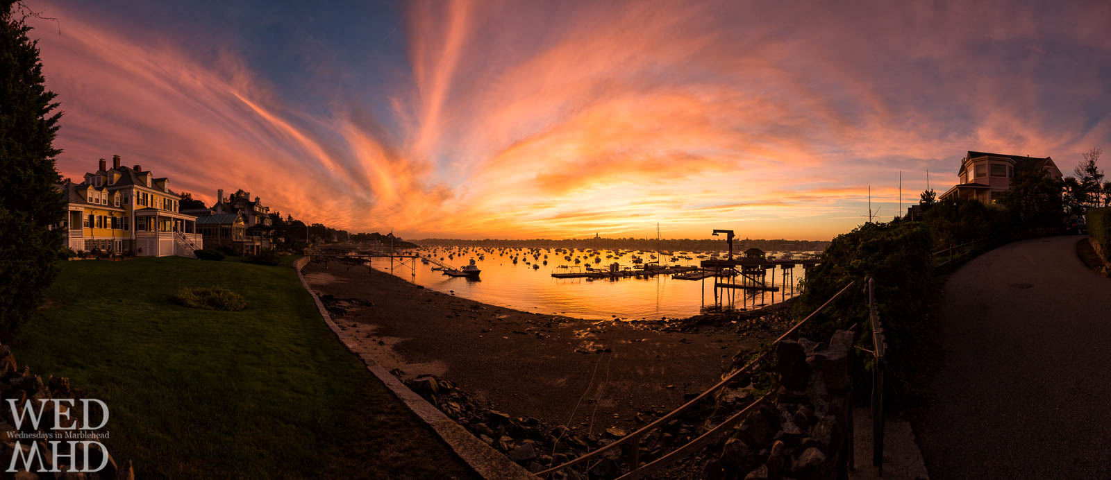 A September sunset creates a breathtaking view from Corinthian Lane as captured in this panorama of stately houses, a harbor filled with boats and reflecting golden light