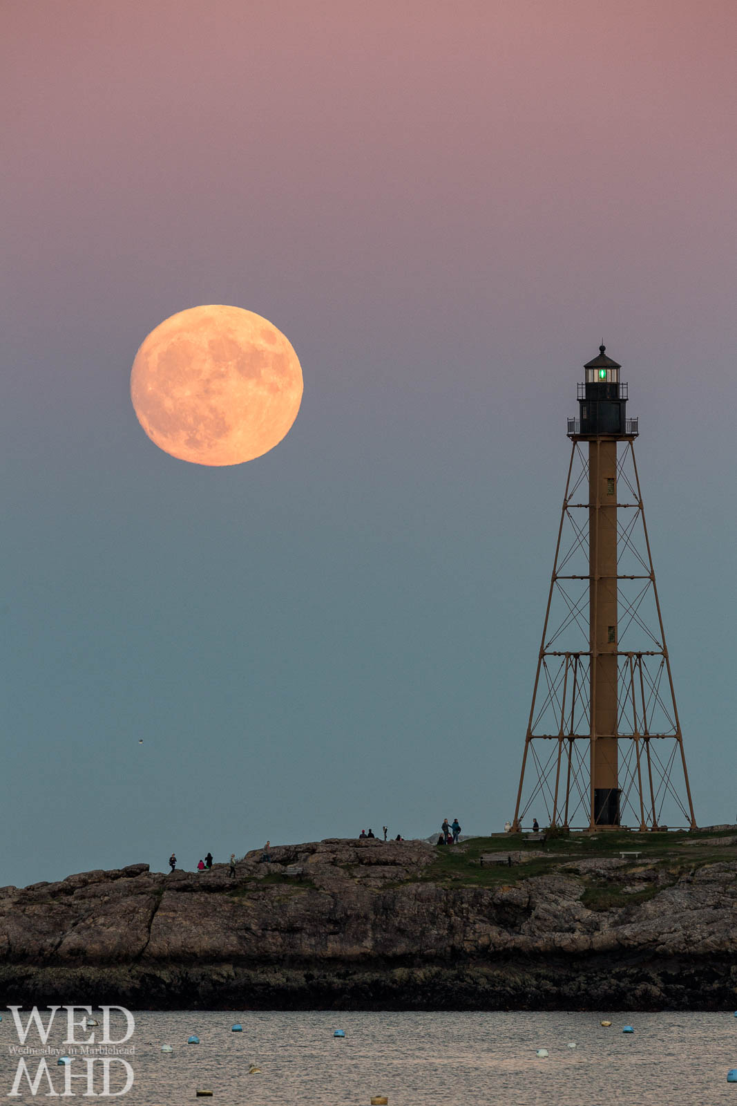 The supermoon rises over Chandler Hovey Park and shines over people gathered to watch the beautiful display with Marblehead Light standing tall with its green beacon lit