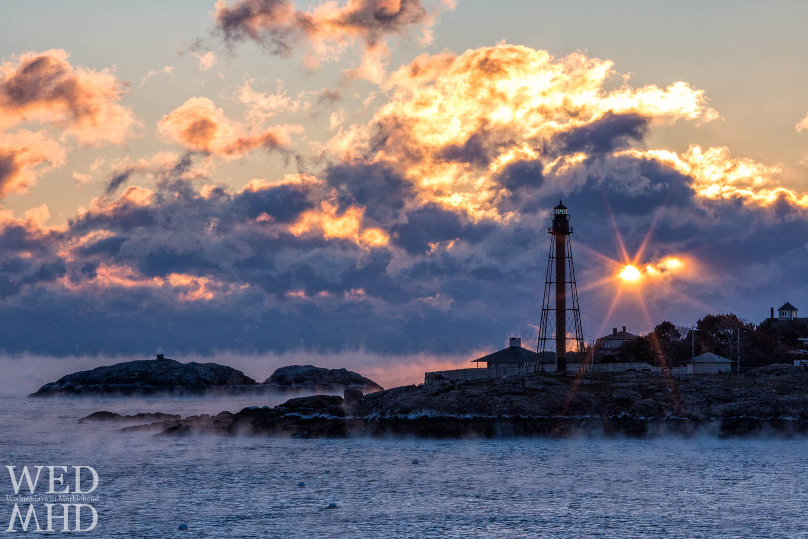 Sea smoke on the water is lit by a fire in the sky as clouds break at dawn over Marblehead Light