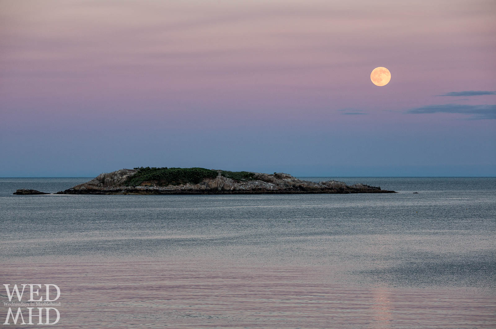 The full buck moon rises over the well-named Ram Island on a mid-July evening surrounded by shades of pink sunset light