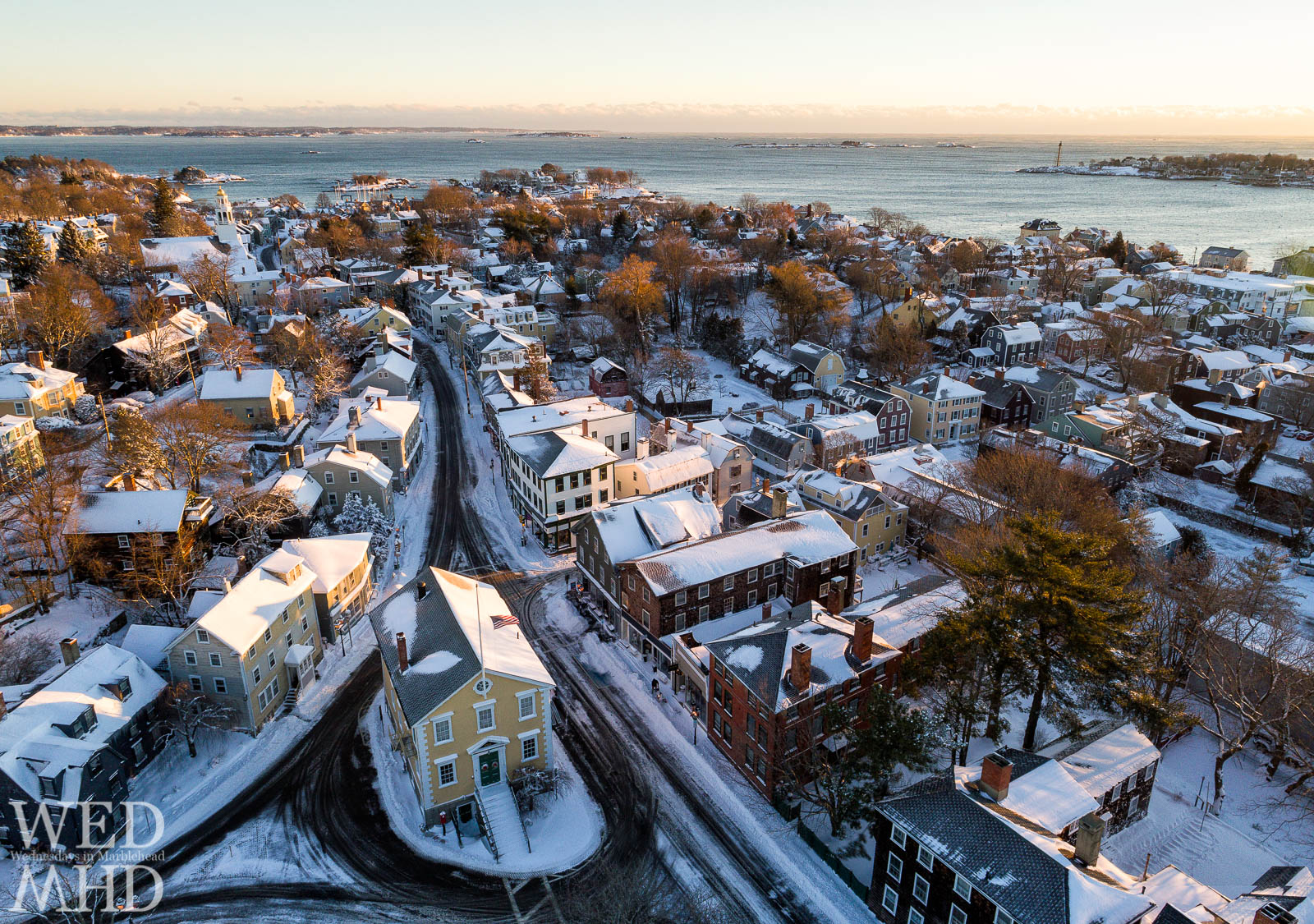 Old Town House and historic downtown are captured on a snowy morning in Marblehead.  The aerial view includes historic homes and Marblehead Light across the harbor.