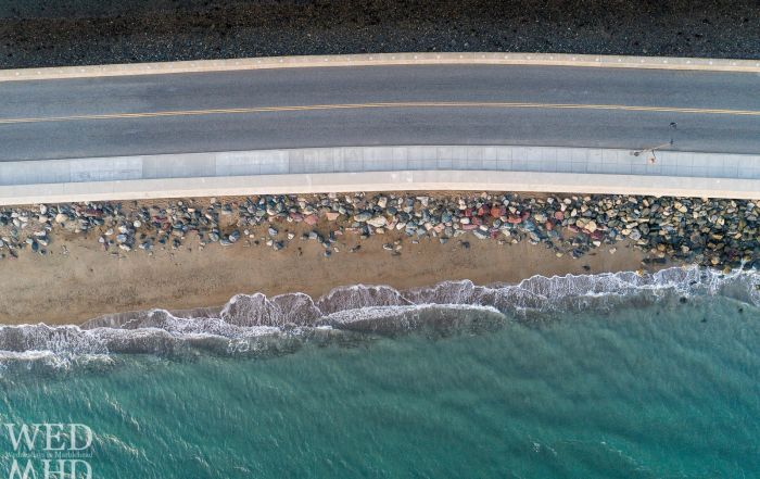 An aerial view of the Atlantic Ocean where waves meet the shore along the Marblehead causeway