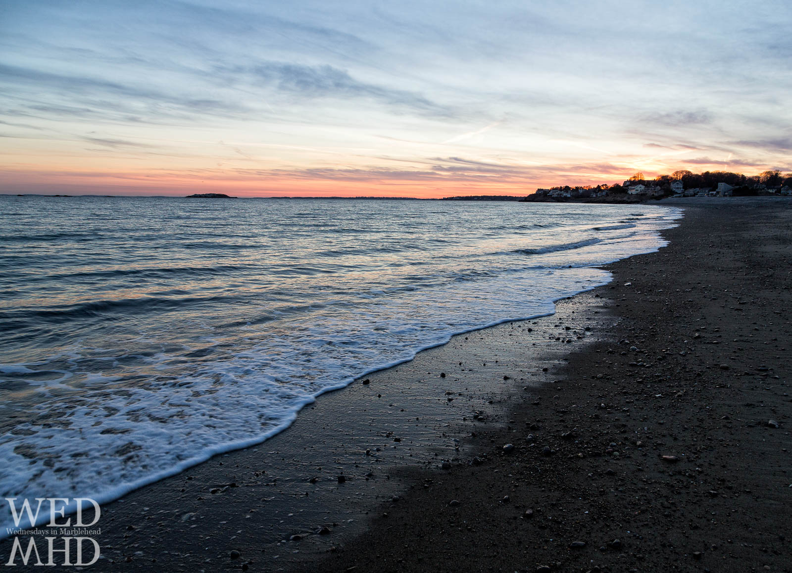 A Winter beach sunset at Devereux Beach with gentle waves coming ashore to form a white surf