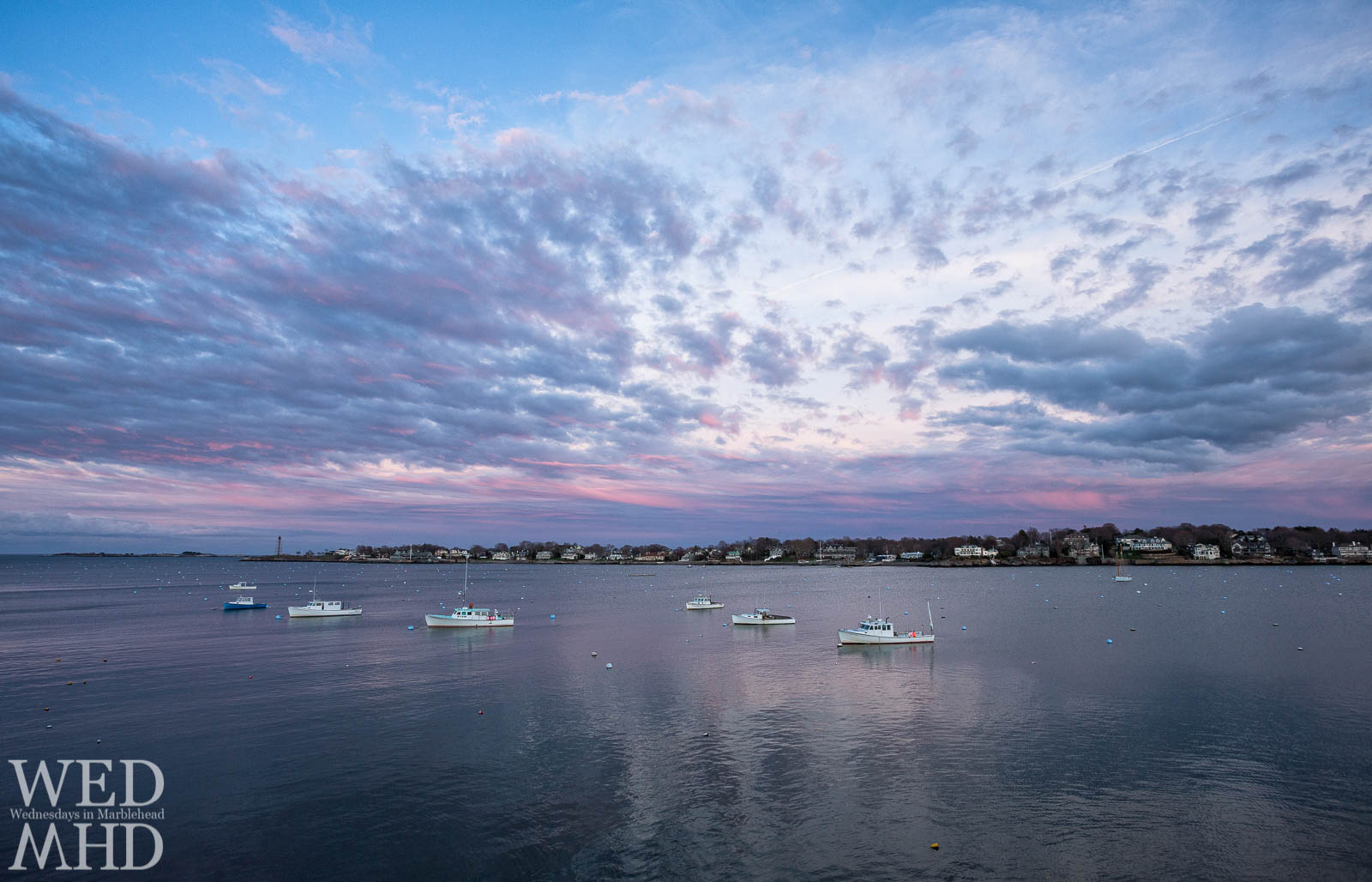 A mid-April sunset shines over the working boats of Marblehead Harbor before the moorings become filled with pleasure boats for the season