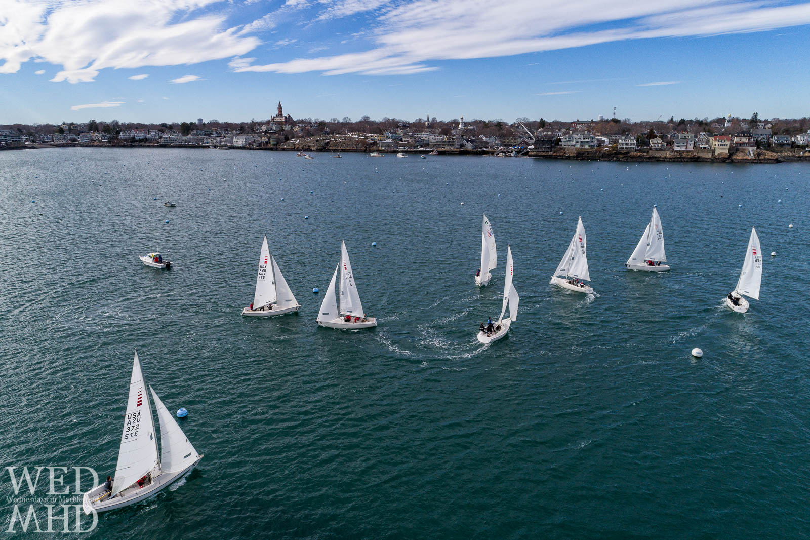 Frostbite sailing takes part under Spring like conditions on a mid-February day in Marblehead Harbor and is captured from fifty feet high by an aerial camera