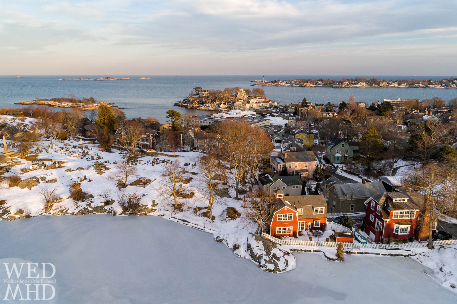 An aerial view of golden light on Redd's pond includes Old Burial Hill, Gerry Island, Fort Sewall and Marblehead Neck