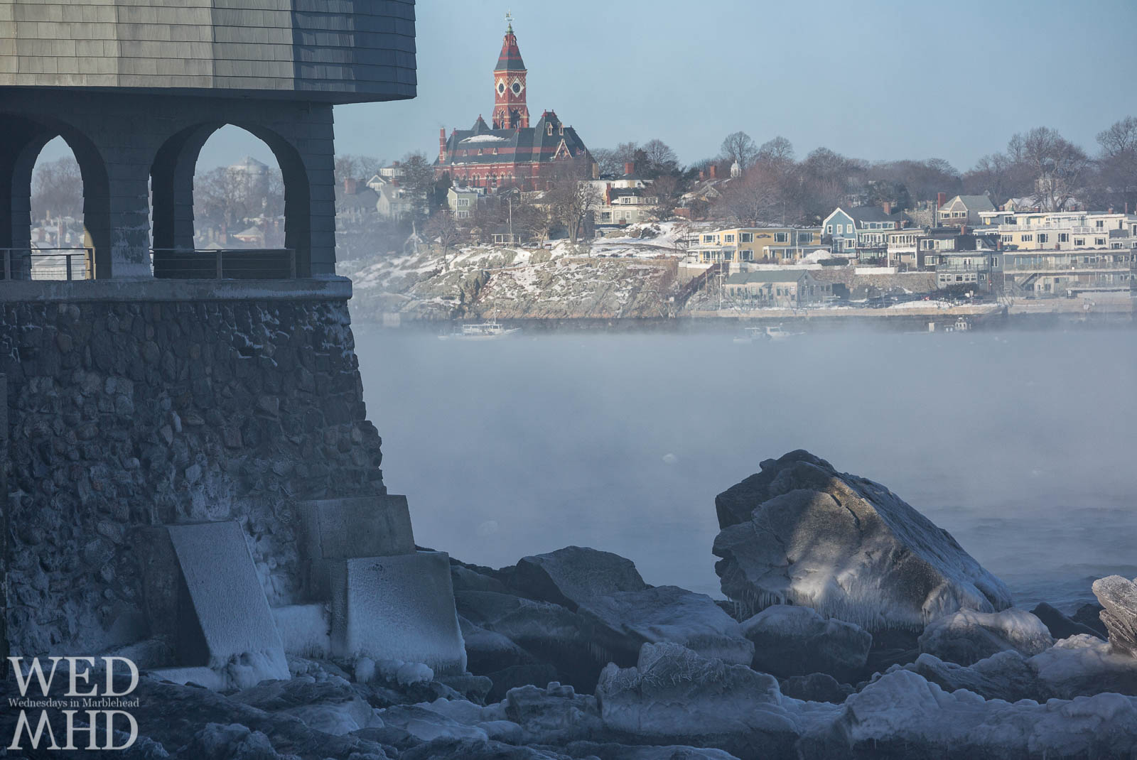 Rime ice forms along the base of the Corinthian Yacht Club with sea smoke creating fog in Marblehead Harbor