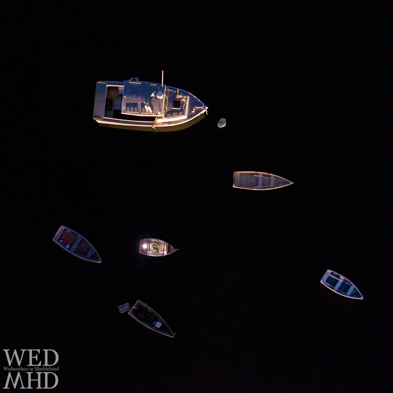 Boats including one holding a Christmas tree are captured from above floating in darkness in the waters of First Harbor