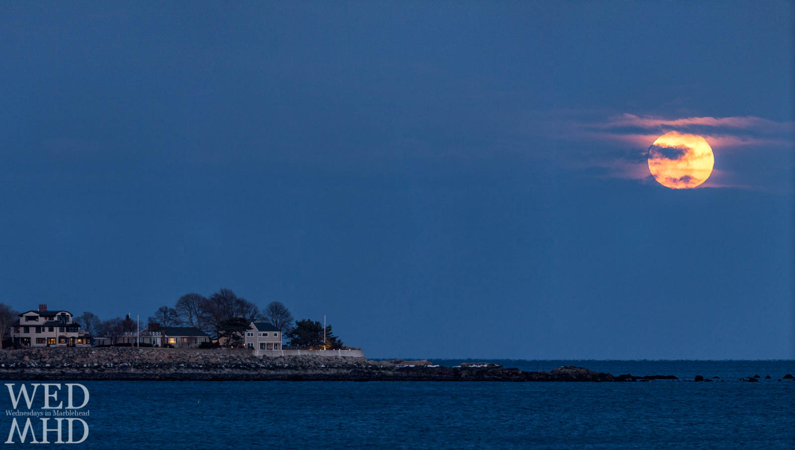 The full worm moon rises on a cold March evening over flying point on Marblehead Neck