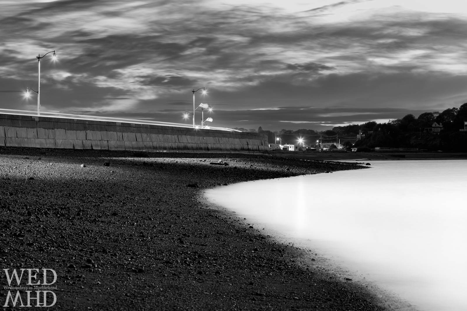 A black and white long exposure image transforms Riverhead Beach to dark stones and milky water with the lights of the causeway shining above