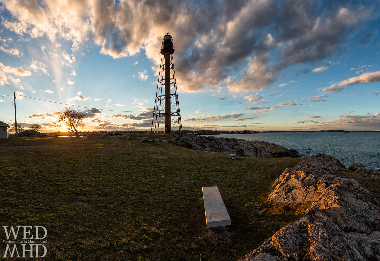 An early March sunset takes shape at Chandler Hovey Park with the lighthouse backed by clouds and the stone bench lit in gold