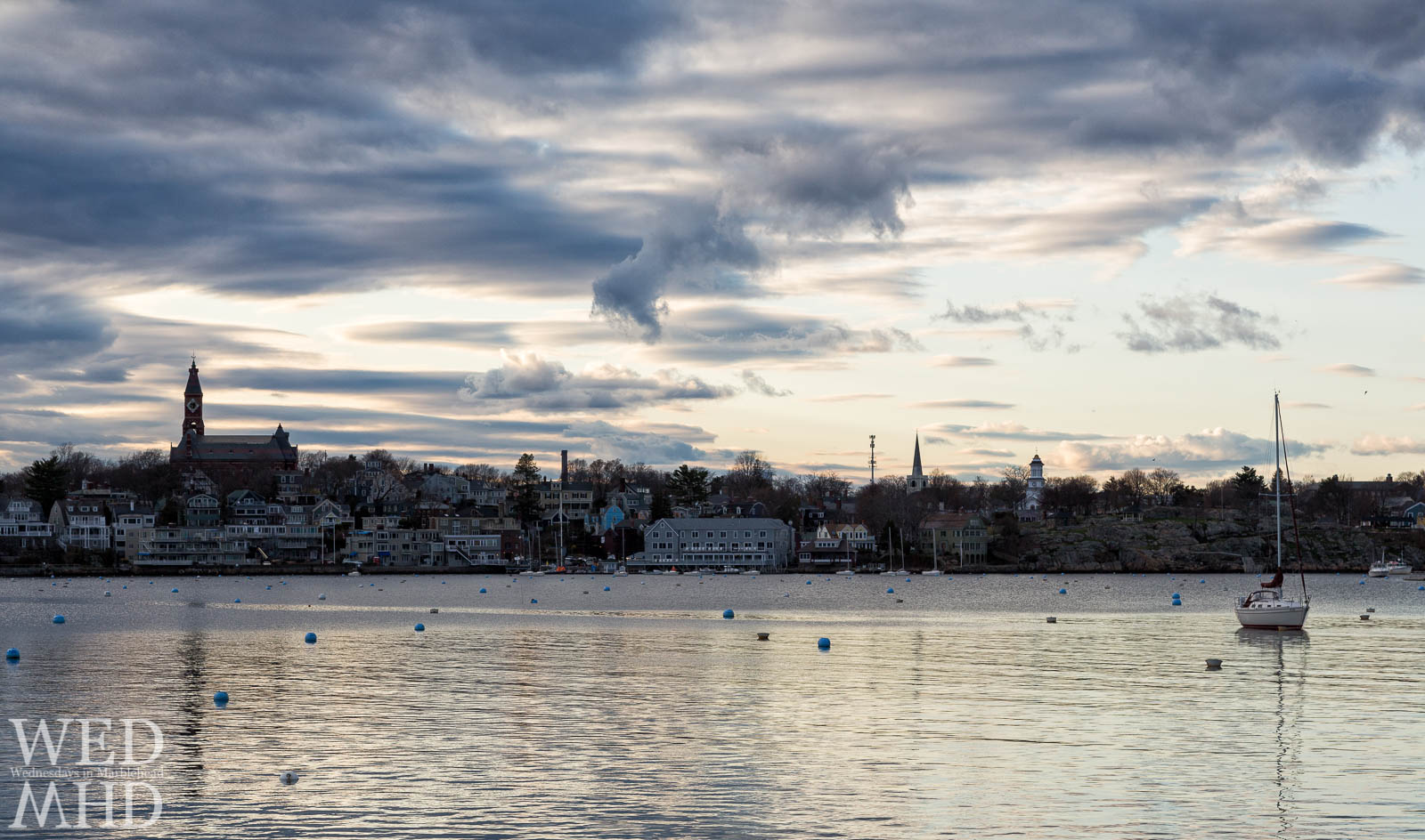 A lone sailboat is moored in the middle of Marblehead Harbor on a late April evening. This may be the first one into the harbor but more will soon follow.